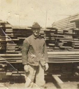 Carl Weinman by lumber. Photo courtesy of Tom Reichard, Carl's grandson.