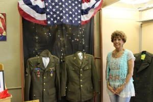 Aleta Weiss by one of the uniform displays. (2015 photo by Karen)