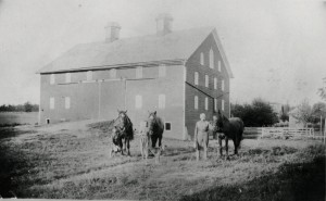 Louis Schumm barn with water tank and windmill on the right. Cornelius, Freida, and Louis J Schumm, 1905.