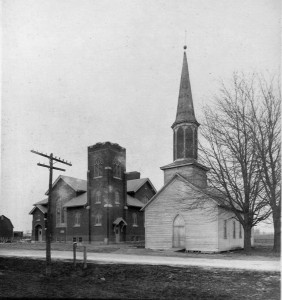 """The frame church and the """"new"""" brick church, side-by-side, until the frame structure was moved."""