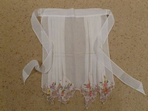 Apron with hankies sewn on bottom.